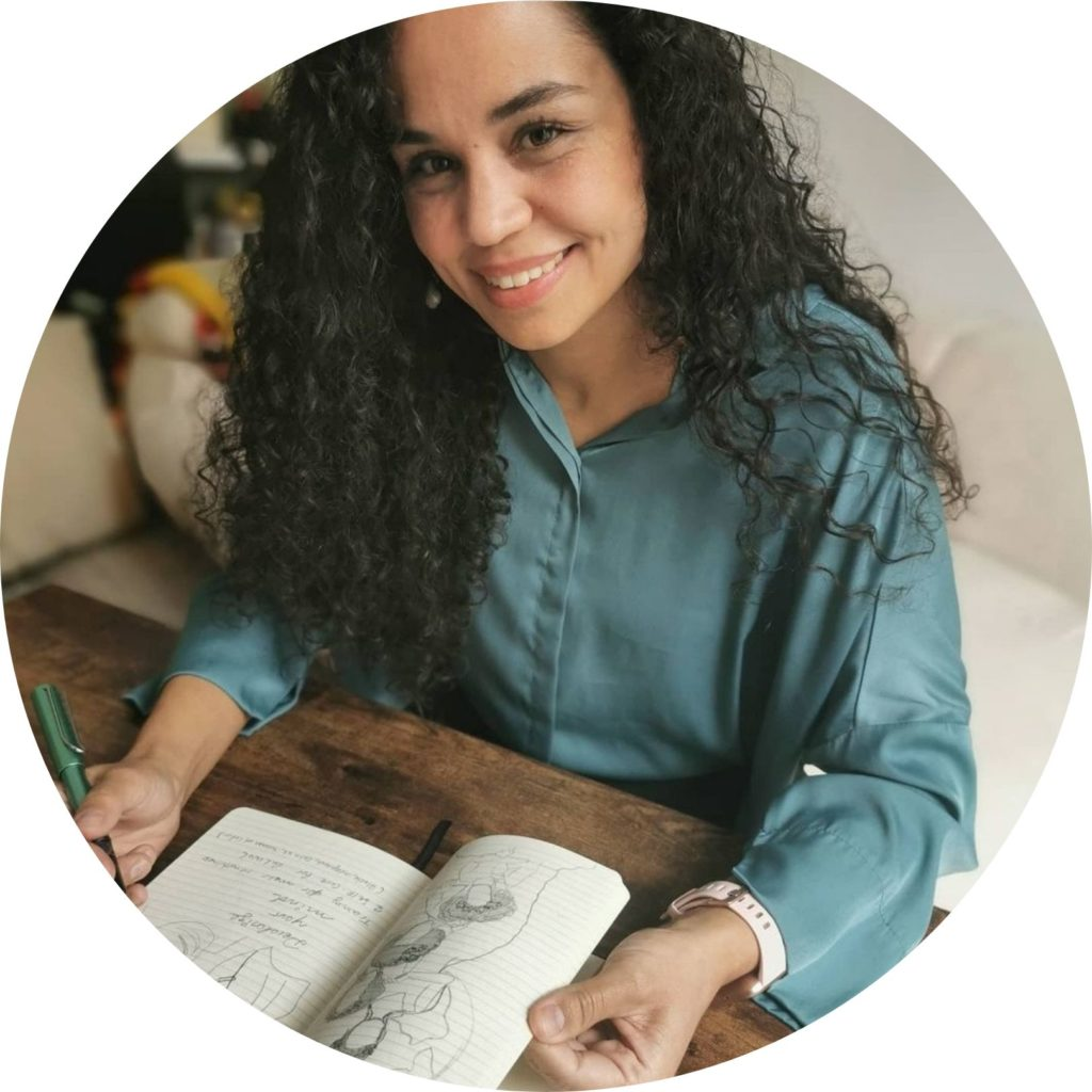 Bild von Mariela Georg sitzend am Tisch und schreibend auf einem Heft.